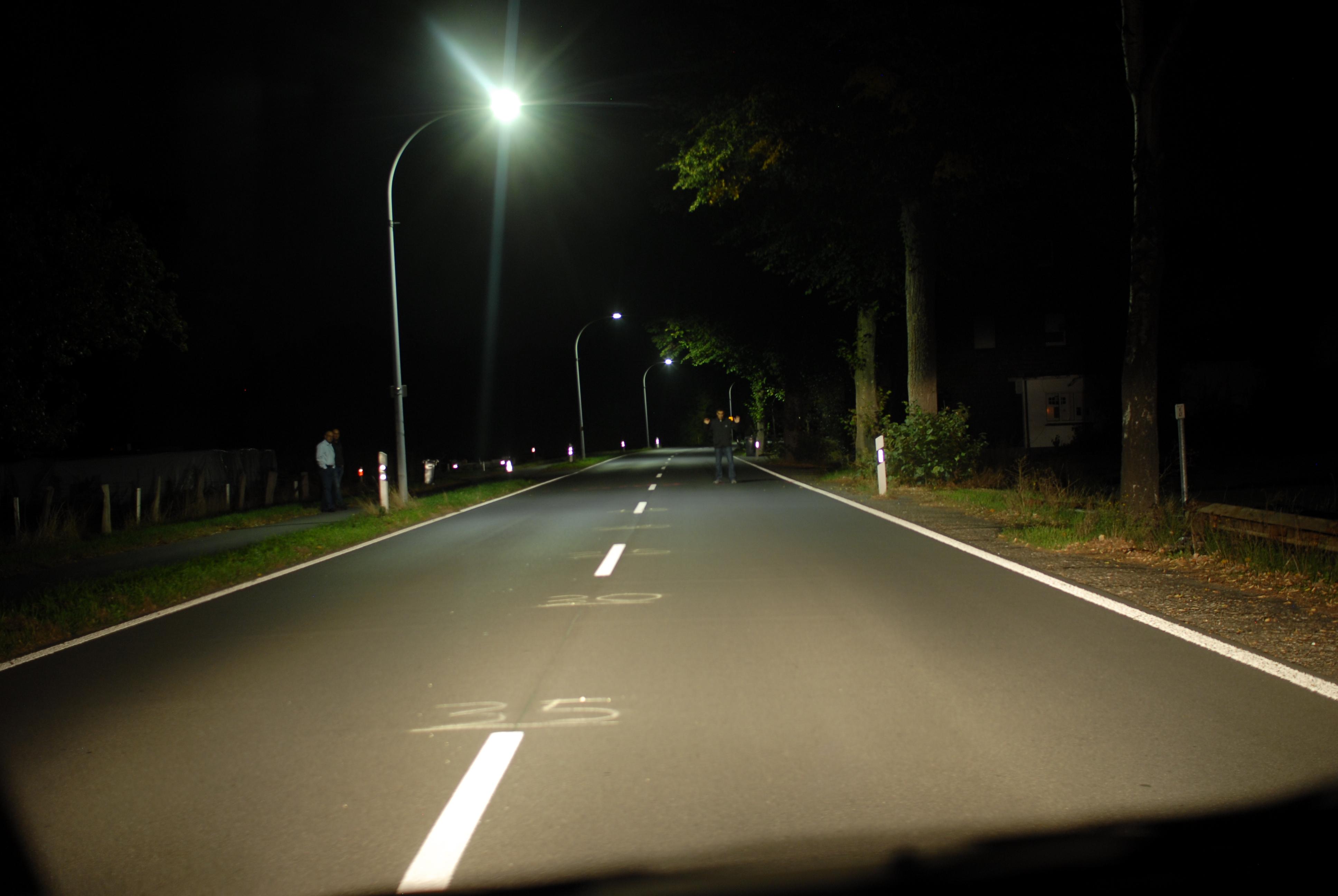 Sicht auf frontal stehenden, dunkel gekleideten Fußgänger aus 40m Entfernung