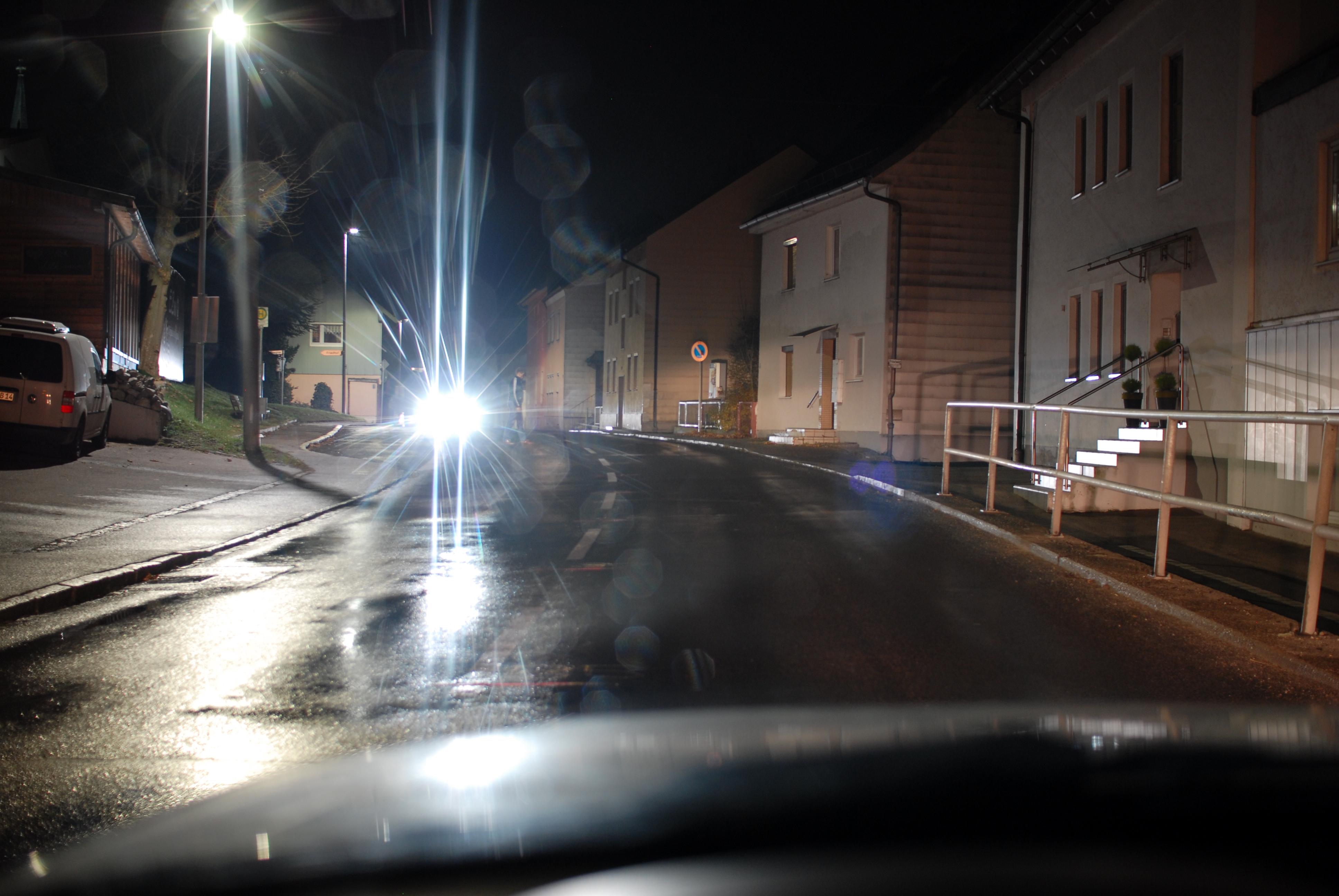 Sicht auf einen dunkel gekleideten Fußgänger mit Blendung durch den Gegenverkehr beim Überfahren einer Kuppe